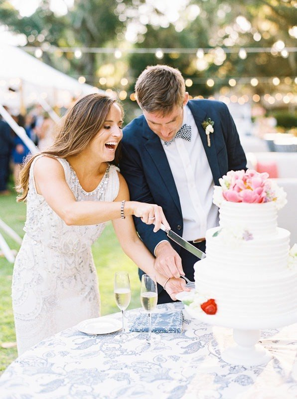 bride and groom cutting cake while laughing