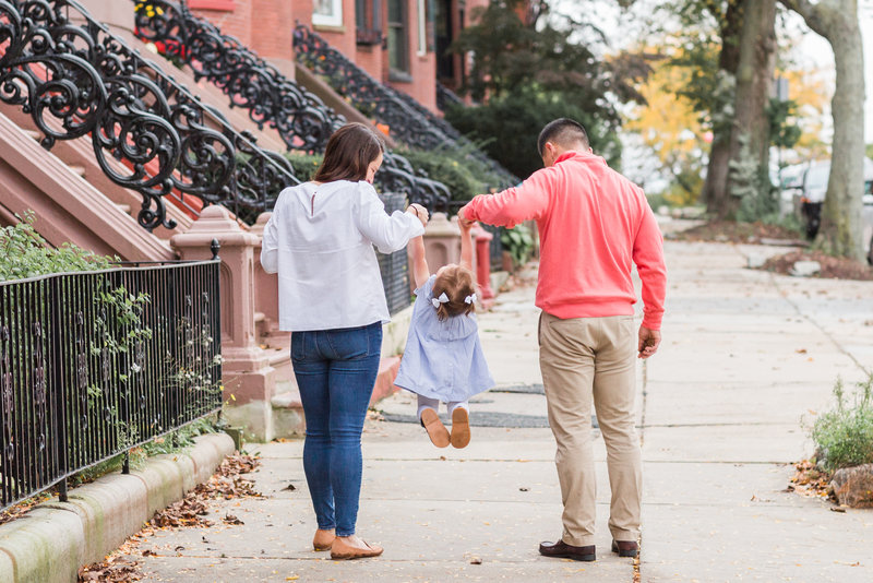 Mom and dad walking with daughter down Boston street