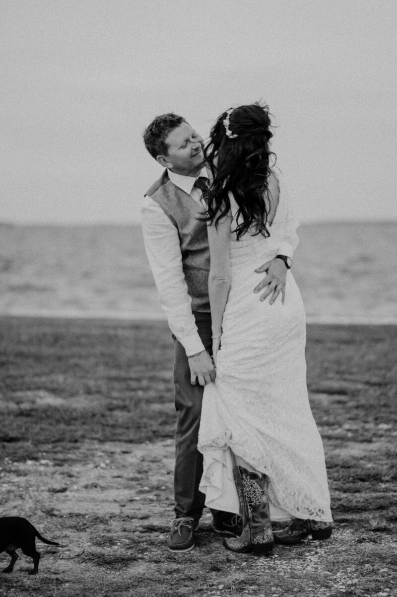 black and white portrait of bride and groom by the water