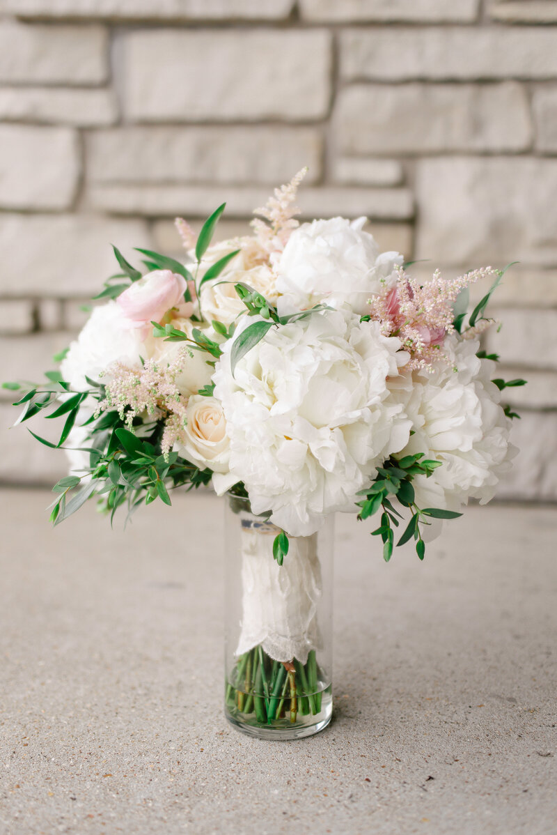 A blush and white bridal bouquet sets near a stone wall.