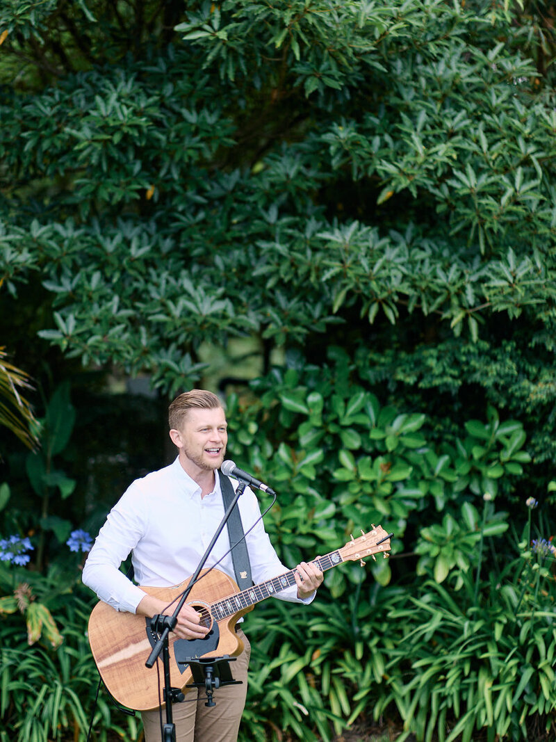 Musician playing guitar and singing in front of garden