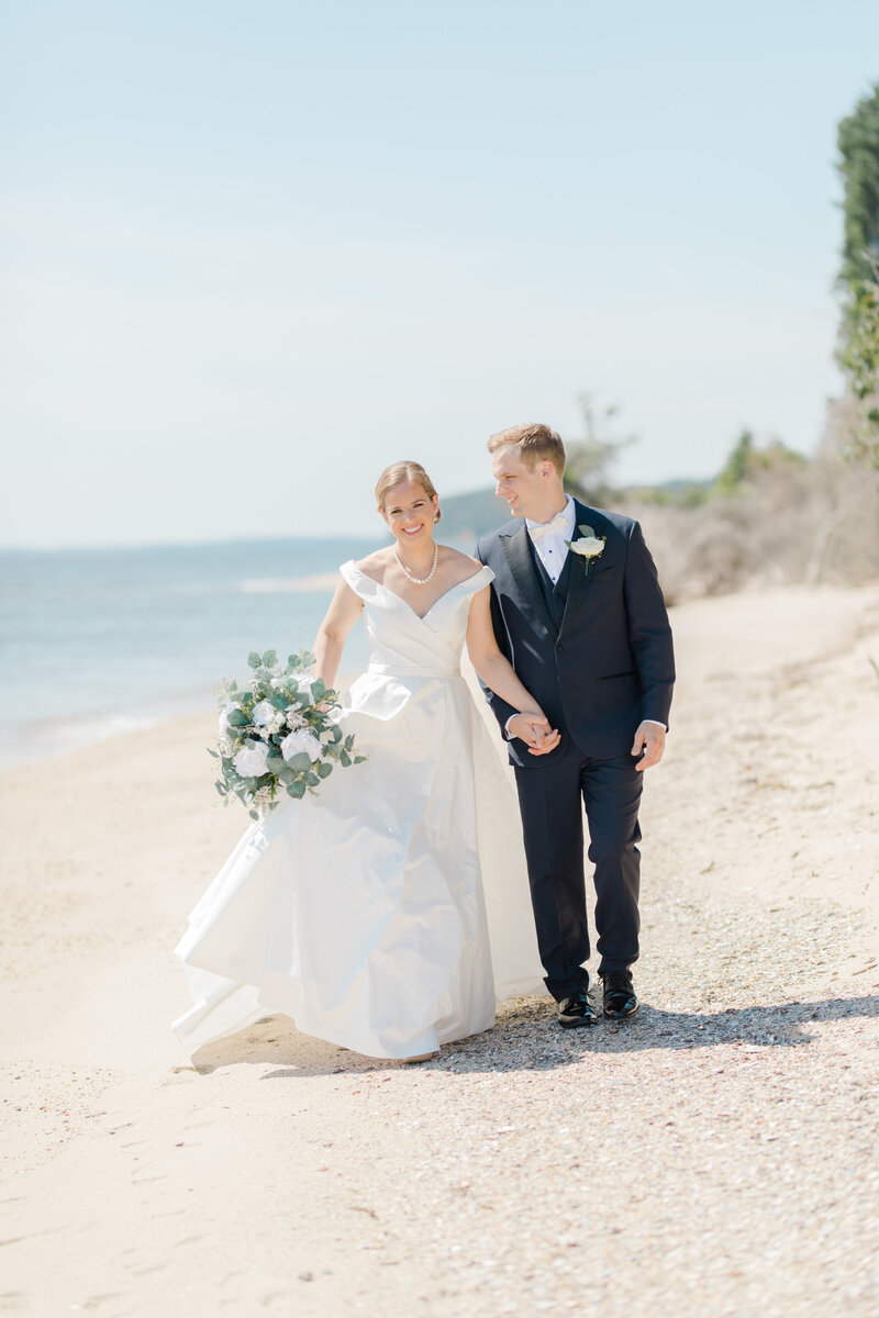 couple walking on beach at Inn at Perry Cabin wedding in St Michaels Maryland by Costola Photography