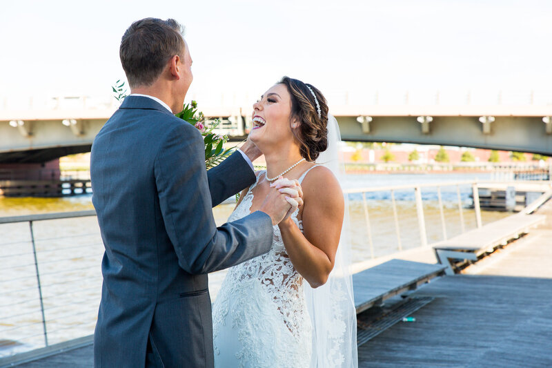 bride and groom see each other for the first time wedding day first look on pier near detroit river