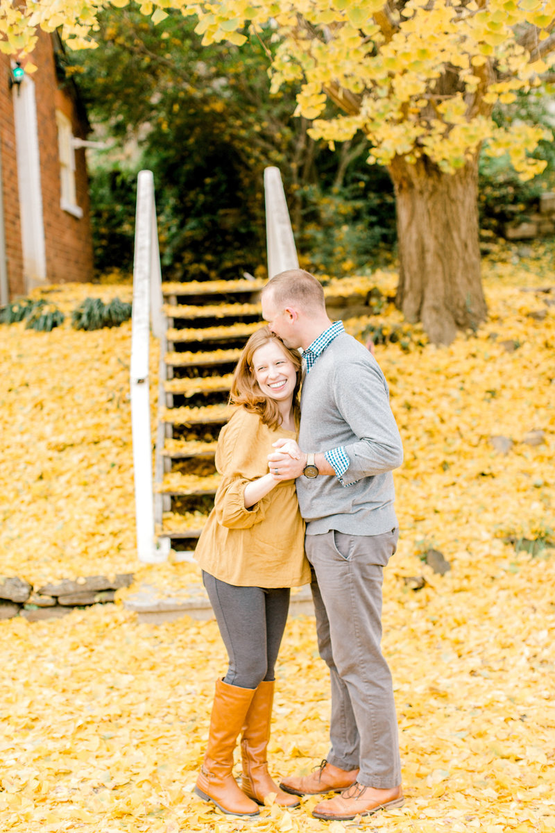 Groom kissing bride at fall engagement session with leaves covering the ground