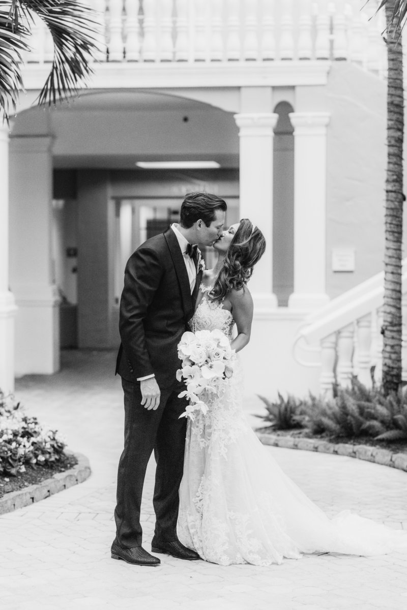 bride and groom kissing in courtyard at Don Cesar Wedding Photographer in St. Petersburgh Florida by Costola Photography