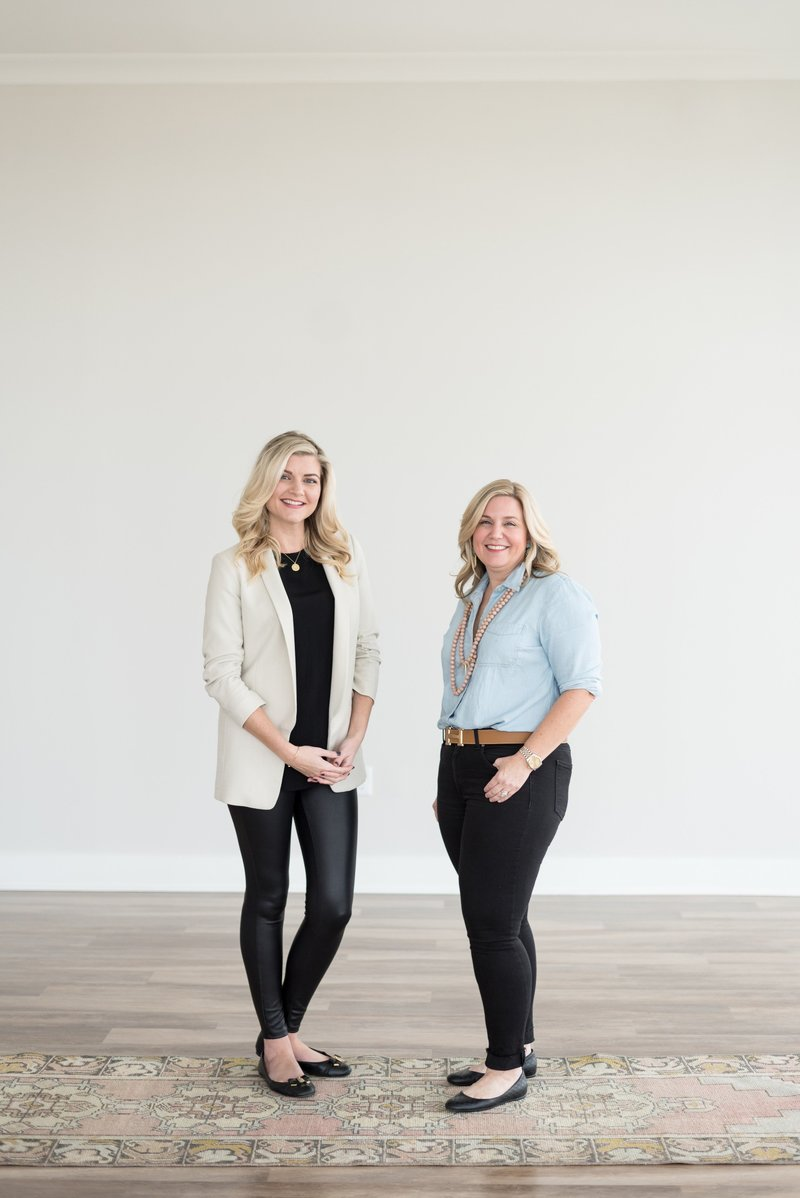 Nashville realtors standing in front of white wall and on a vintage rug for business headshots