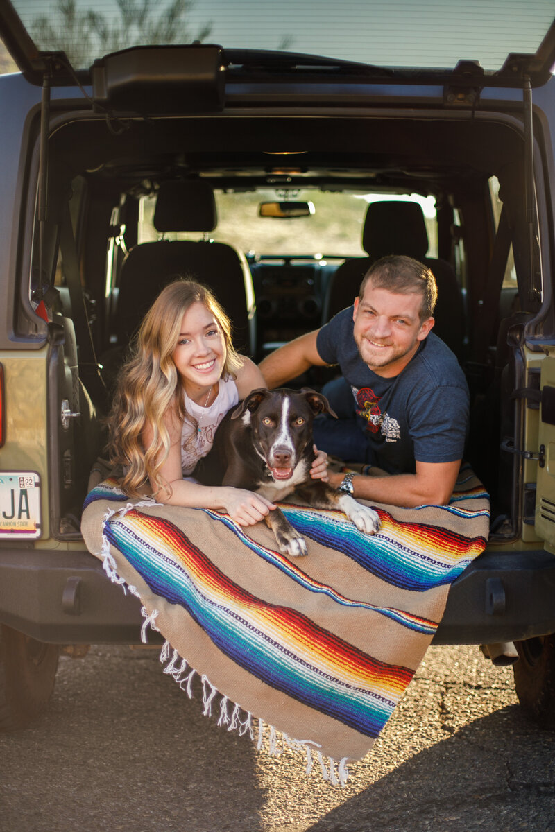 Makayla laying in her jeep wrangler with her boyfriend and dog