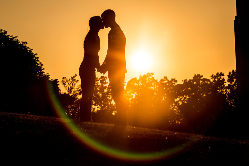 A silhouette of a couple kissing at sunset.