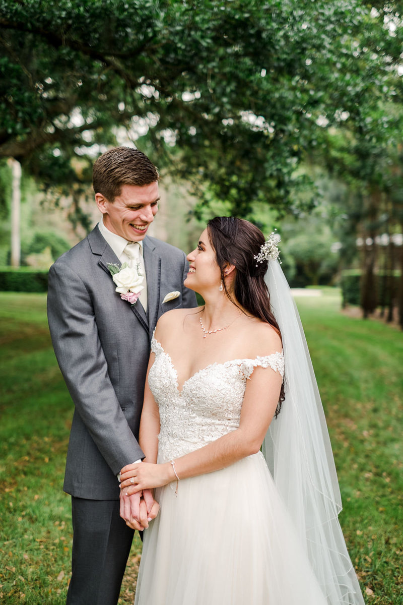 Latin American bride and Caucasian groom smiling at each other on their wedding day