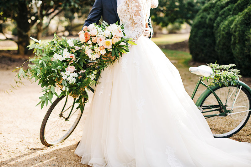 bride and groom pose with a floral draped tandem bike