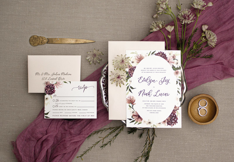 Hydrangeas, Peonies, Ranunculus and Anemone flowers are beautifully painted in watercolor around the invitation. Leafs and blooms peak from behind the oval shape creating depth, beauty and interest.