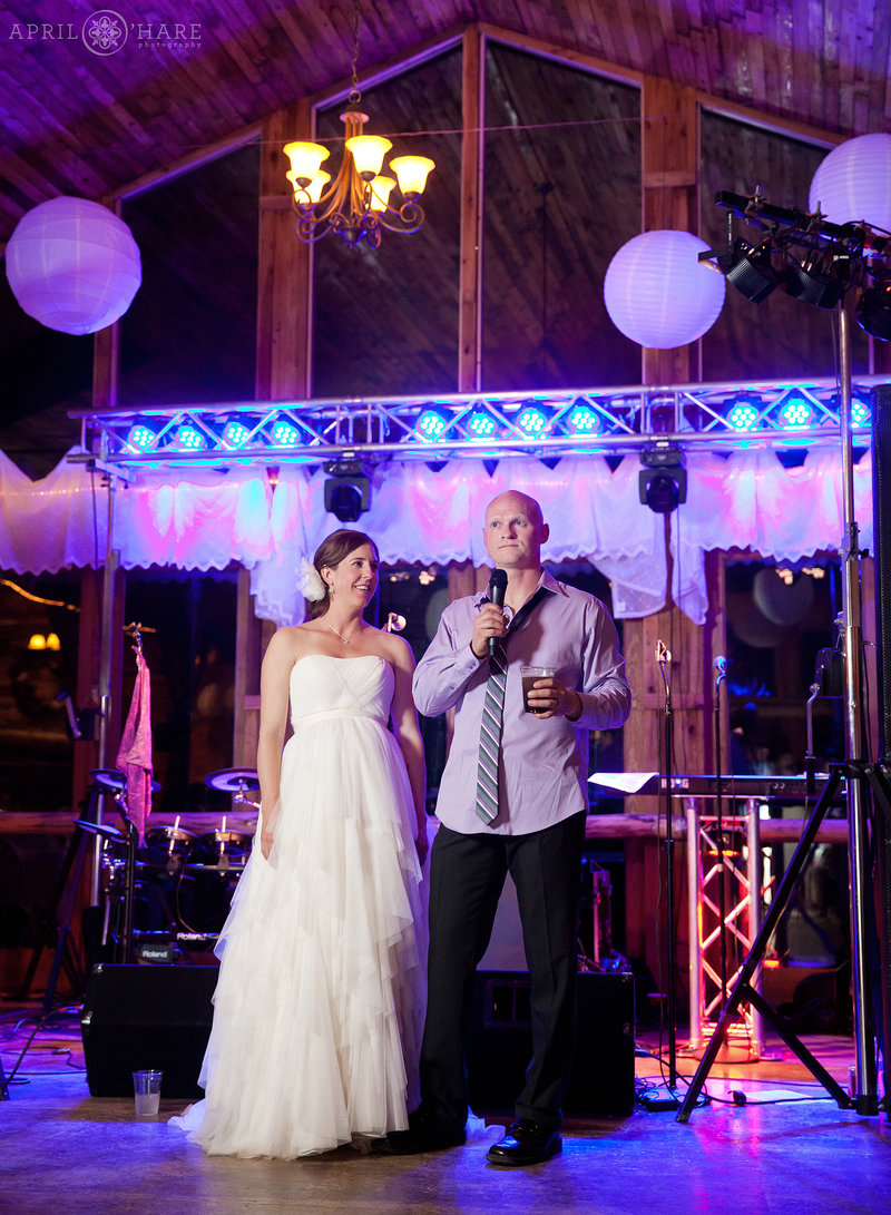Bride and groom at barn wedding reception with purple lighting Colorado