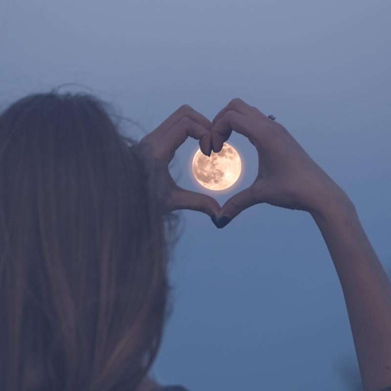 A woman making a heart shaping it around the moon as she looks at it
