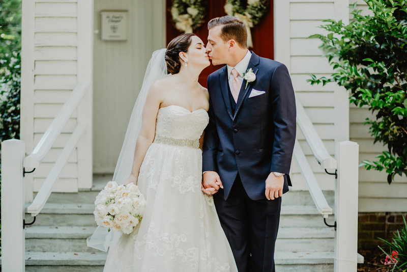 Bride and Groom kiss in front of white church in Magnolia Spring Alabama