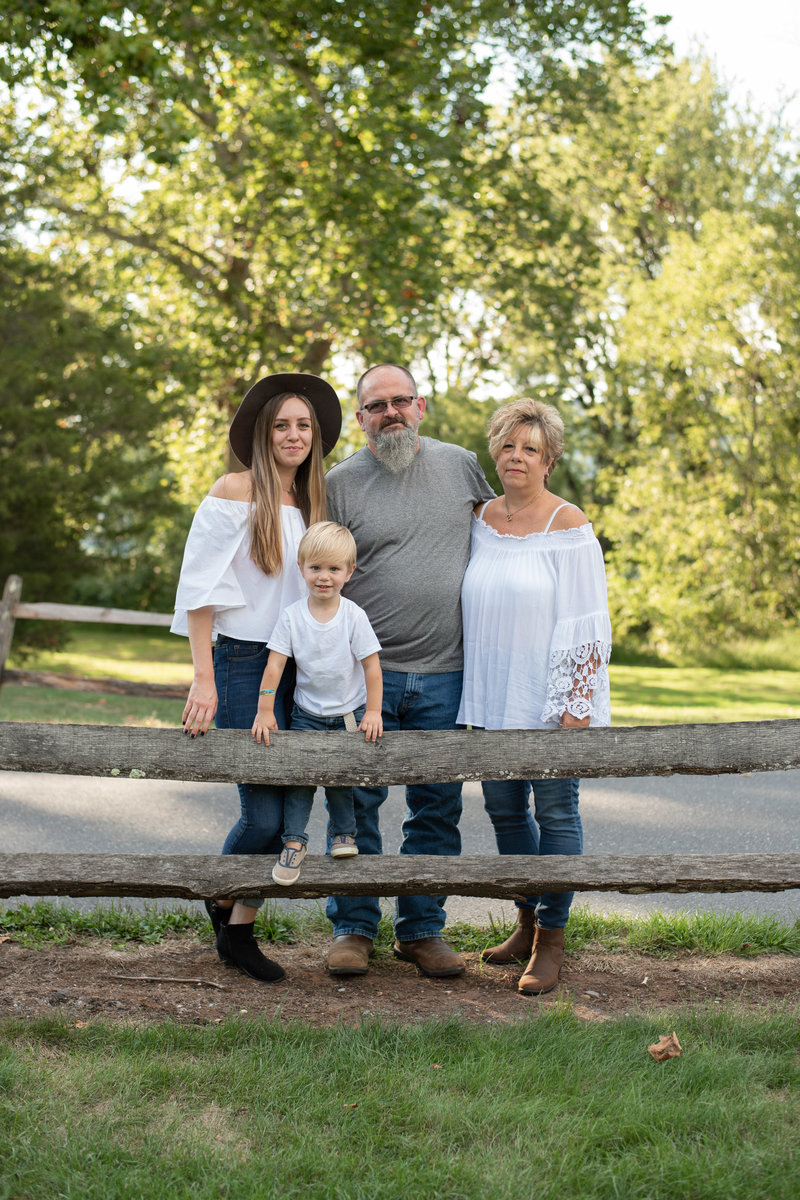 Family of four posed behind a wooden fence with trees behind them.