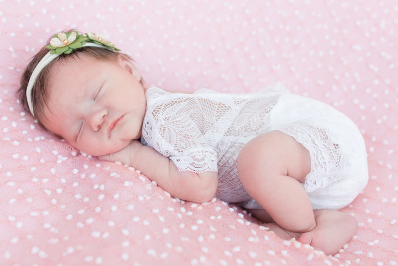 Newborn baby girl sleeps atop a pink and white speckled coverlet during newborn photography session