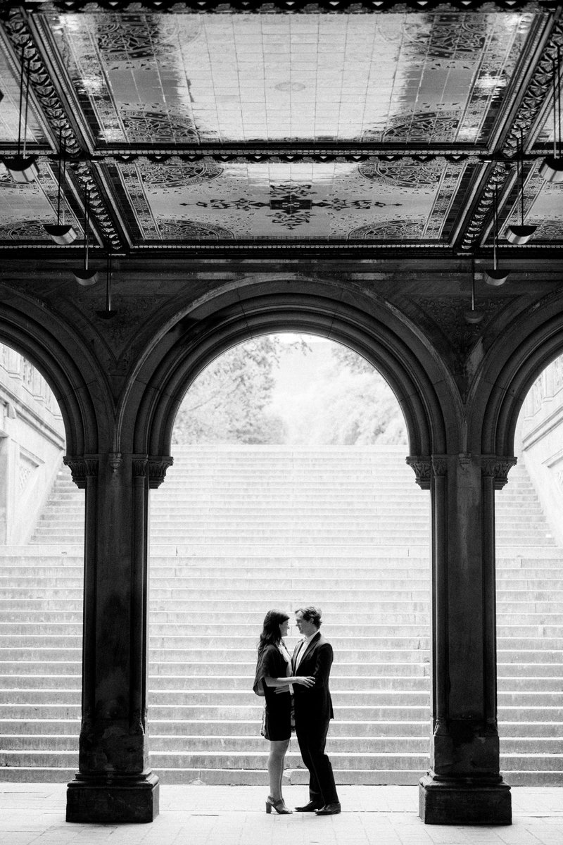 Couple stands in archway in Central park for best Central Park engagement photos