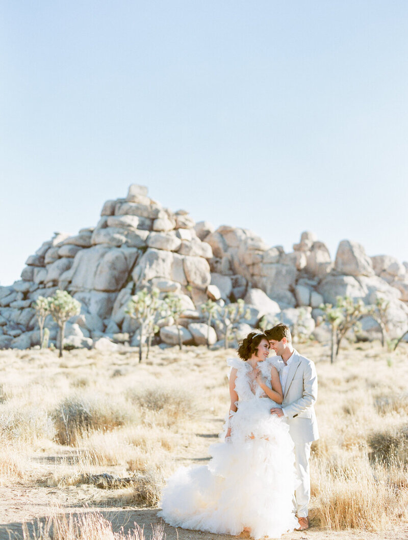 bride  in a poofy wedding dress and groom in a tan suit with their foreheads together with a rock formation and palm trees behind them in  Joshua Tree National Park