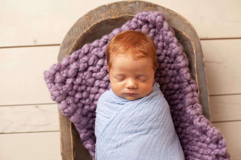 red headed newborn baby girl in purple and brown wooden bowl