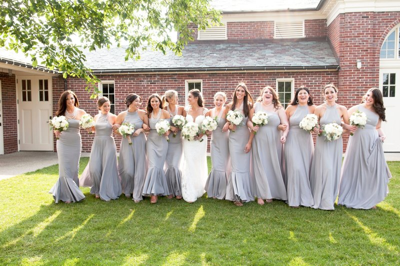 Large bridal party in pale purple blue bridesmaid dresses with white bouquets