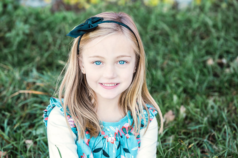 A girl with sparkling blue eyes is captured in the grass in CT