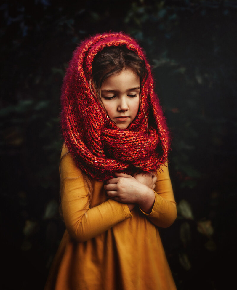 Young girl embraces herself in marigold dress and red head scarf