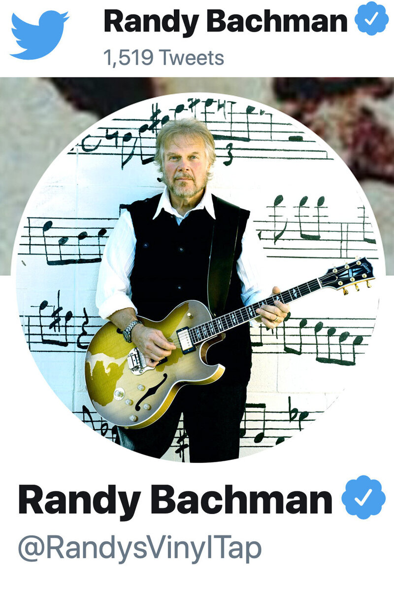 Randy Bachman Twitter profile photo standing in front of wall with musical notes painted on it holding guitar