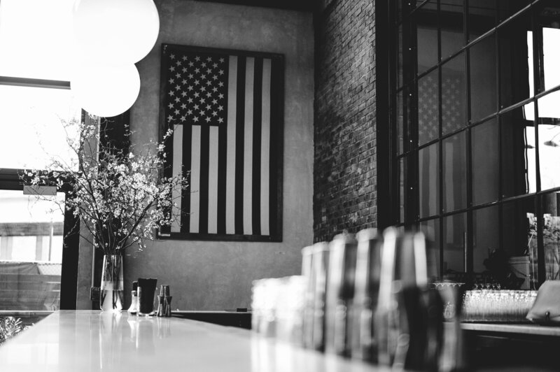 a black and white photo of a blurred bar in the foreground with plants on the left bar supplies on the right and american flag hanging on the brick wall philadelphia distilling company shot by philadelphia wedding photographer alex medvick