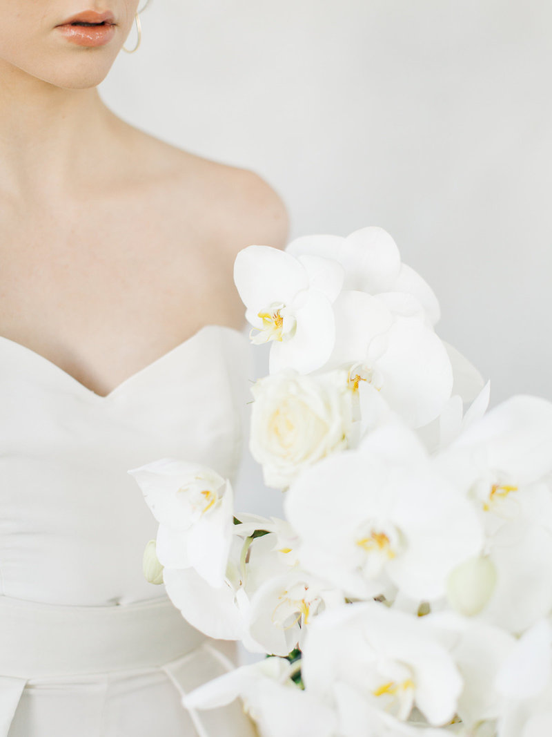 bride wearing pant suit with cape wedding dress holding an all white orchid bouquet