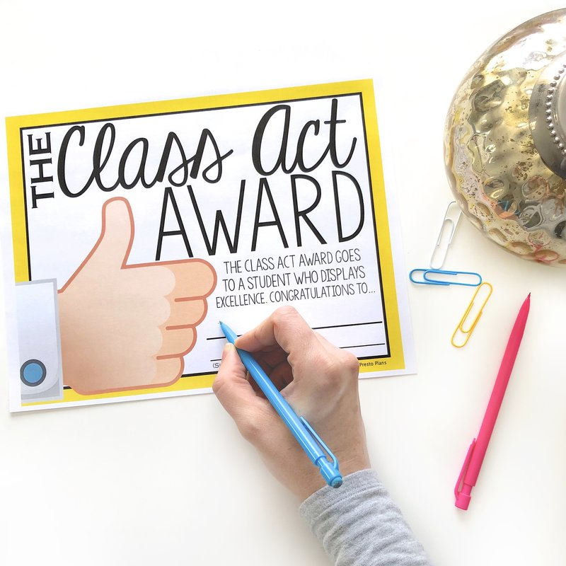 A teacher writing on an end of the year  student award where each award relates to a different idiom.  In this one, the award is the class act award and it goes to a student who displays excellence.  The award is beside a pencil, paperclips, and a decorative jar.