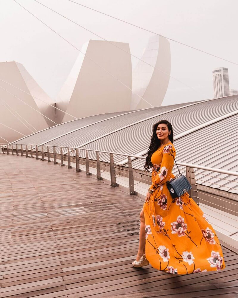 Isabella walking in yellow dress - luxury travel blogger