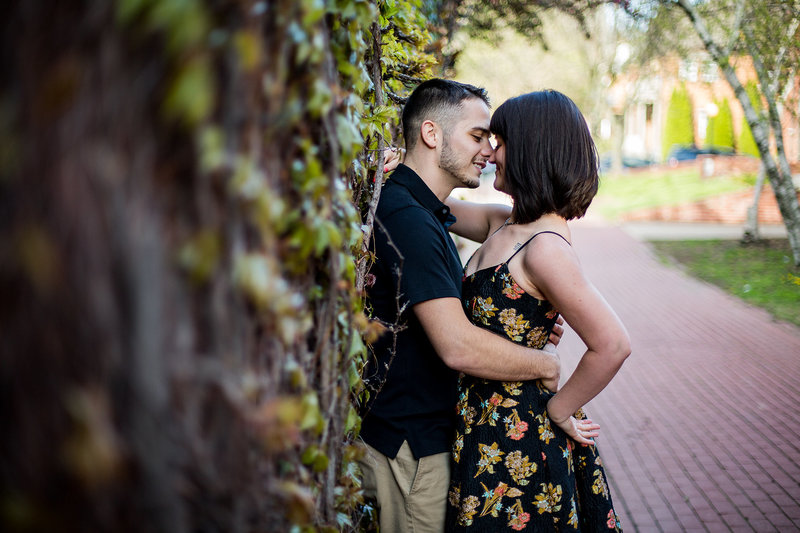 Man and woman are about to kiss during engagement photos in Modern Tool Square