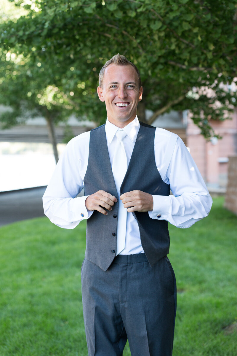groom buttoning up suit on wedding day