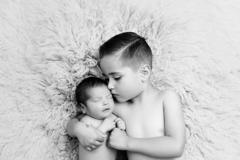 big brother sibling holding newborn