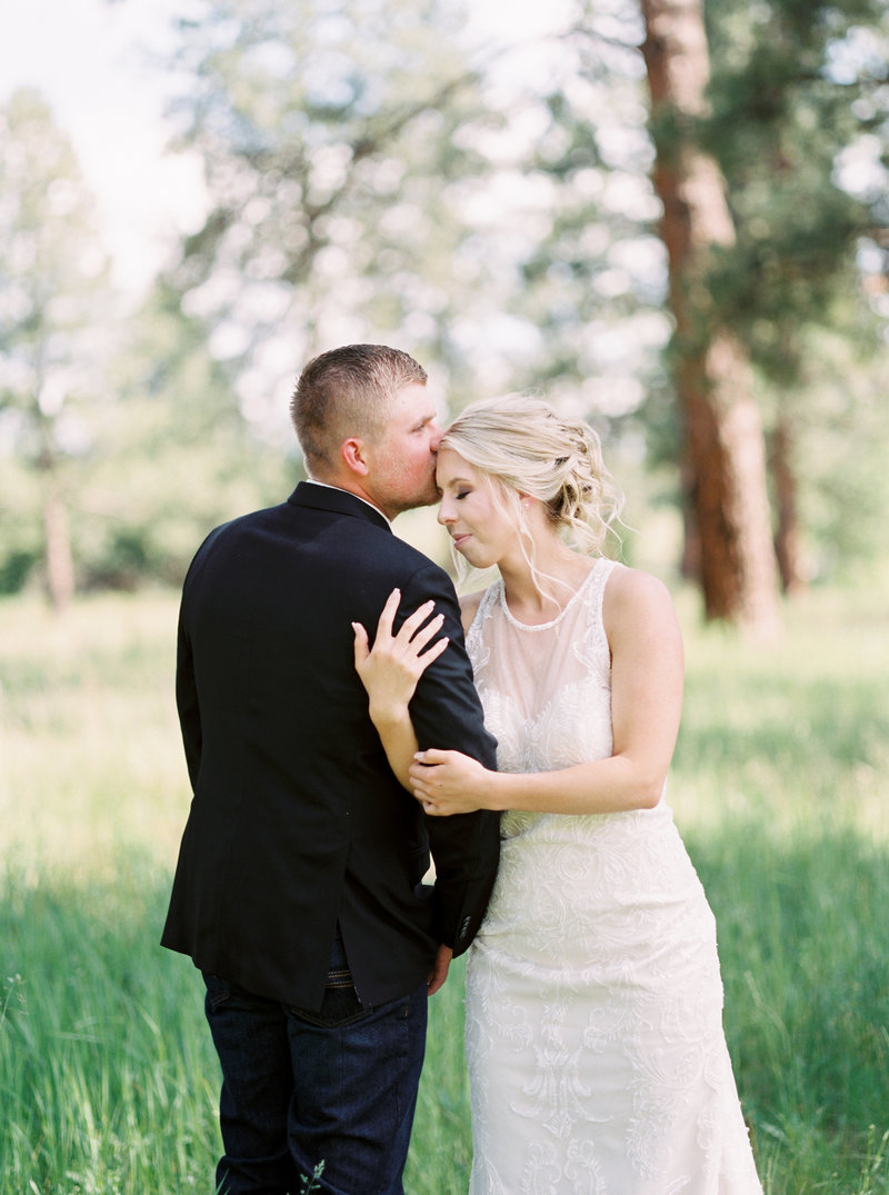 bride and groom kissing in forest