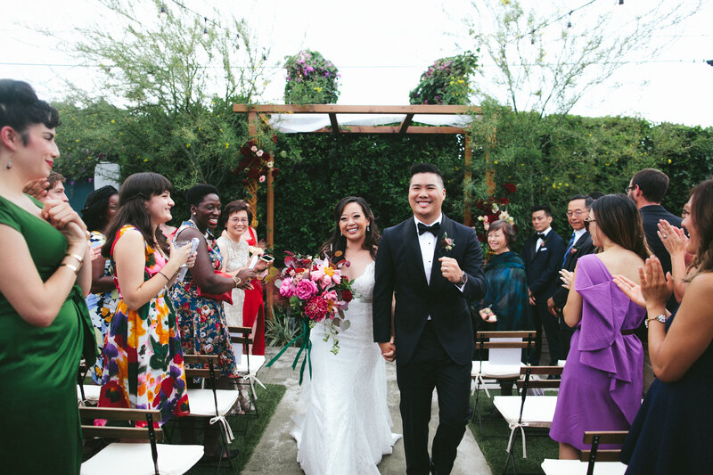 Bride and groom smile brightly while walking back down the aisle as a married couple
