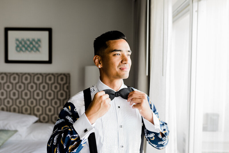 groom with bowtie getting ready