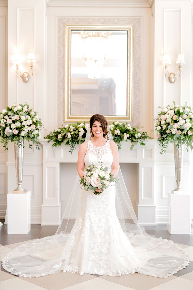 Bride in wedding dress posing with flowers and professional hair and makeup in Toronto