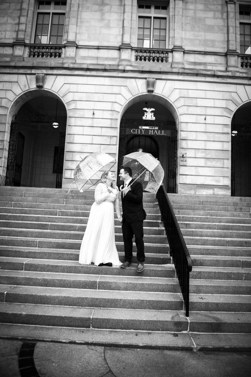 Bride & groom smile at each other under umbrellas on the steps of Portland City Hall after their wedding on a rainy day in Portland, Maine