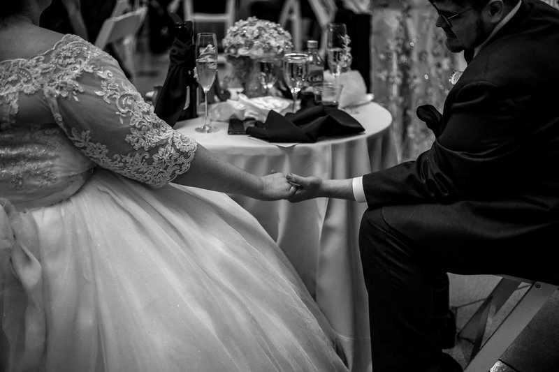 Bride and groom hold hands under their table during Warner Theatre wedding reception