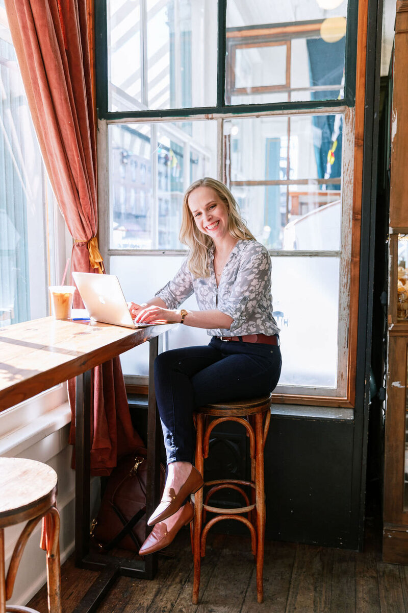 Digital Grace Design owner and Showit website designer, Sarah Blodgett, sits in a French inspired cafe on a stool in front of a window and smiles while working on her laptop with an iced coffee