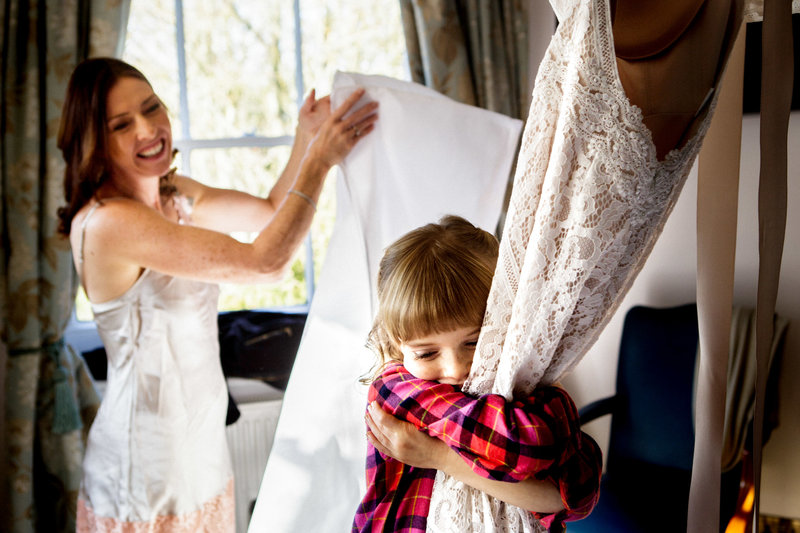 bride's daughter hugging wedding dress