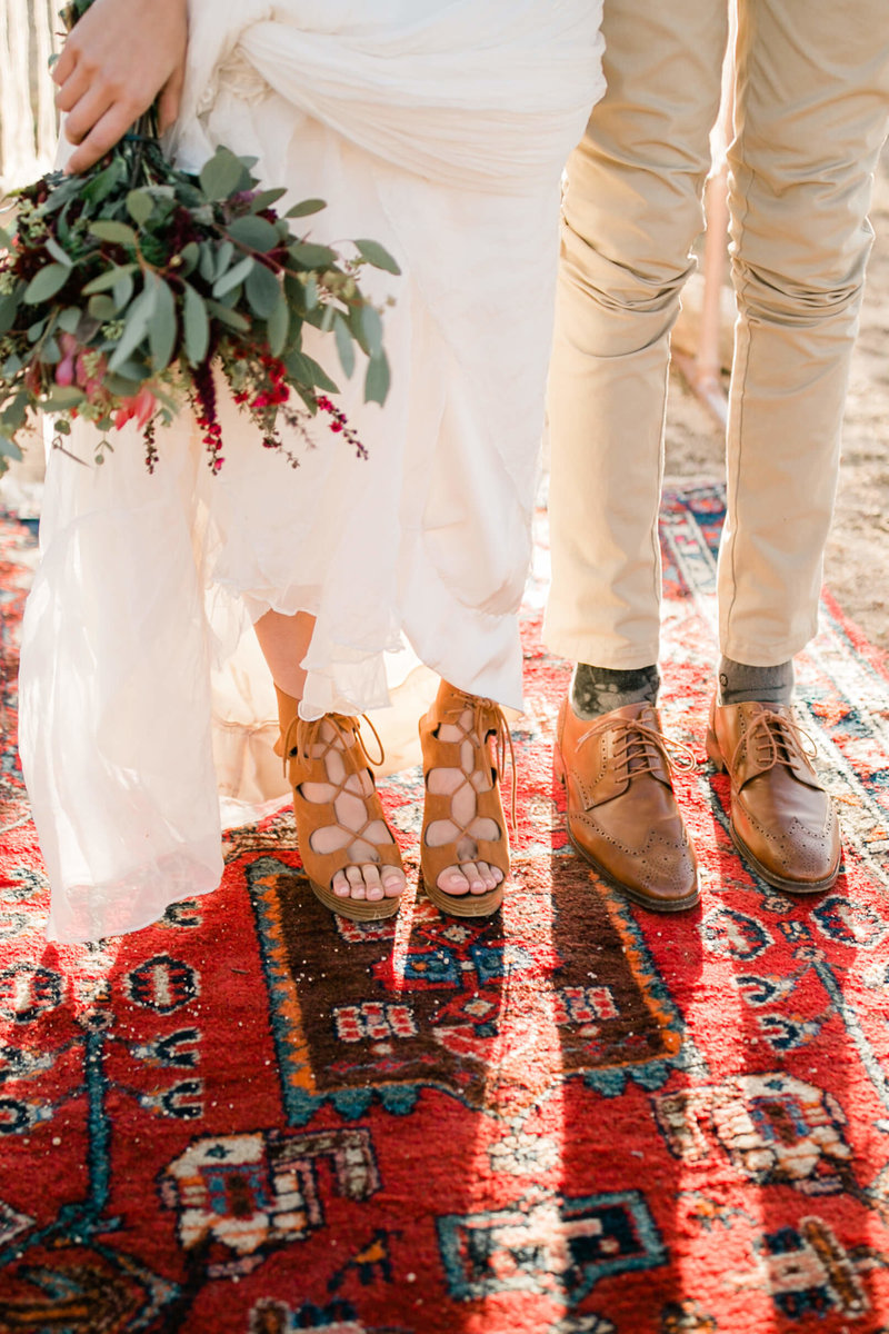 elopement details of the brides shoes. bouquet, and dreamy boho rug