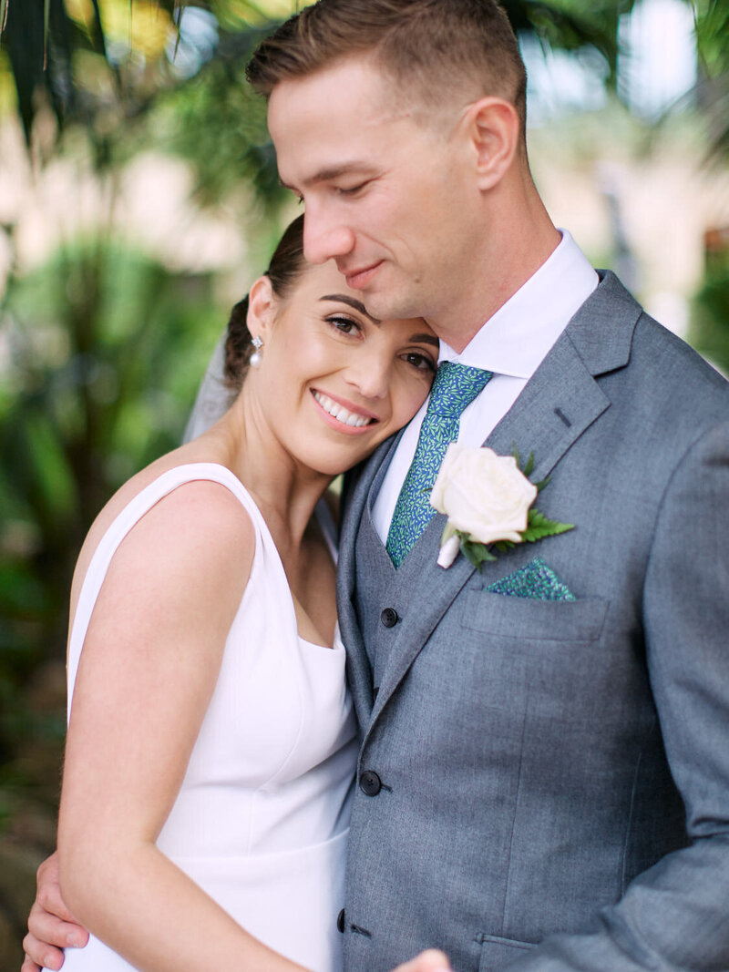 Bride snuggling into grooms chest and looking at camera