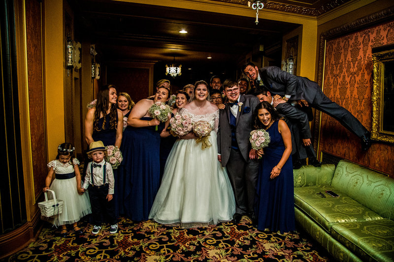 Bridal party goofing around for portraits in the lobby of the Warner Theatre