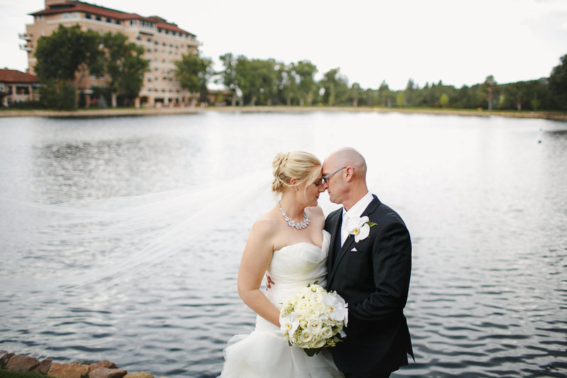 Bride & Groom embracing on their wedding day in front of lake with veil blowing in the wind