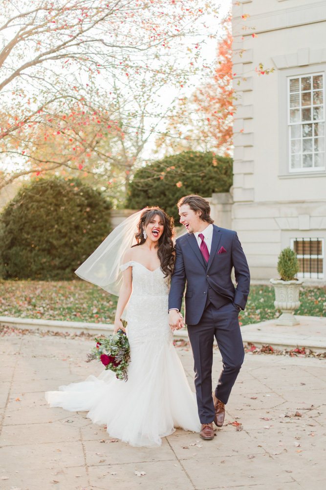 couple walking and laughing outside of manor at great marsh estate wedding in northern virginia by costola photography