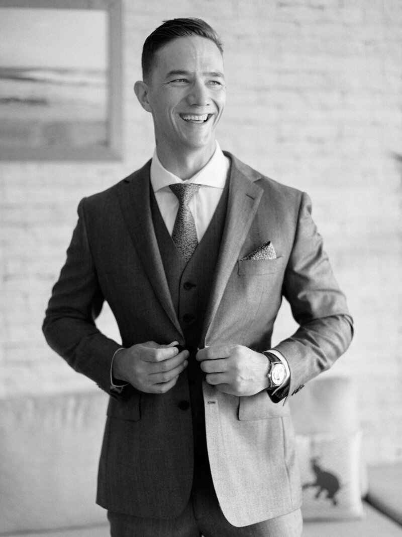 Groom buttoning up suit jacket and laughing