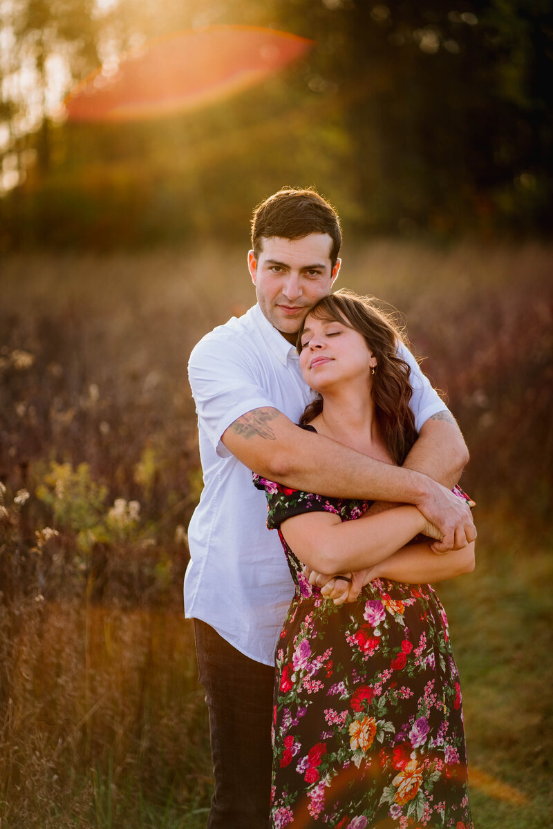 couple cuddled in a field during golden hour