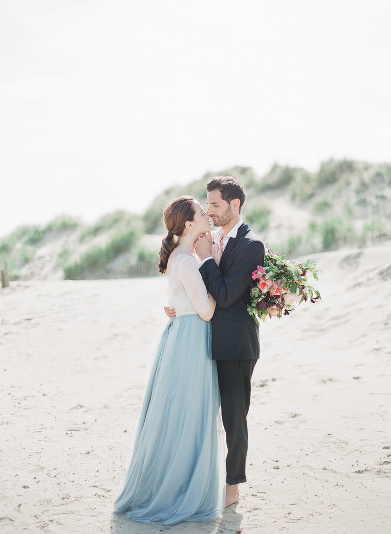 UK wedding planner & stylist | Fine art English coastal elopement. Bride wearing blue tulle gown and holding a bouquet, with groom wearing a black tux